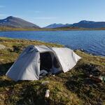 Mitt tält utanför en lugn fjäll damm